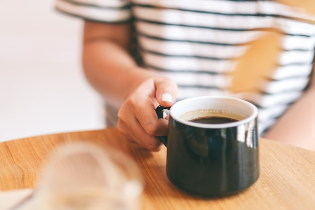 Крупным планом изображение женской руки, держащей зеленую чашку горячего кофе на деревянном столе