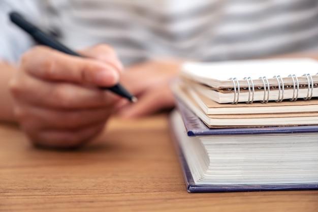 ノートや木製のテーブルの本に書くためにペンを持っている女性の手のクローズアップ画像