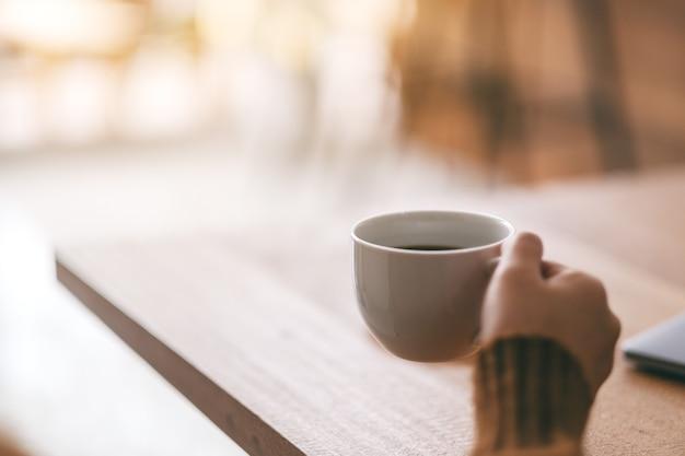 뜨거운 커피를 마시기 위해 흰색 컵을 들고 있는 여성의 손을 클로즈업한 이미지