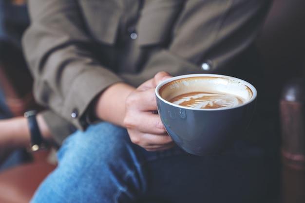 Крупным планом изображение руки женщины, держащей и пьющей горячий кофе латте, сидя в кафе