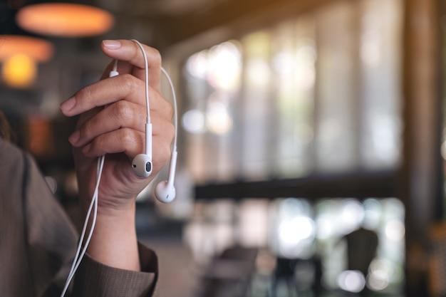 카페에서 음악을 듣고 이어폰을 들고 여자의 손의 근접 촬영 이미지