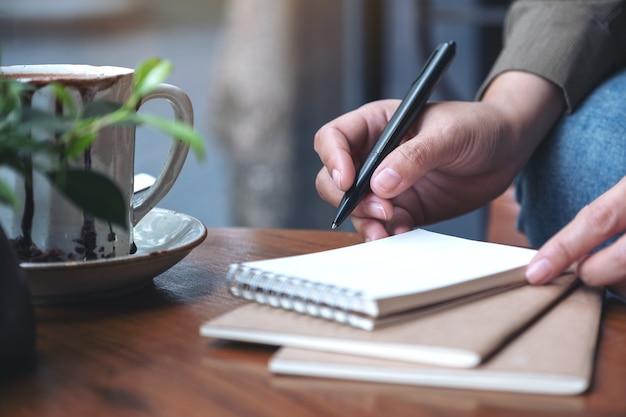 Крупным планом изображение руки женщины, готовящейся писать в пустой блокнот с чашкой кофе на деревянном столе