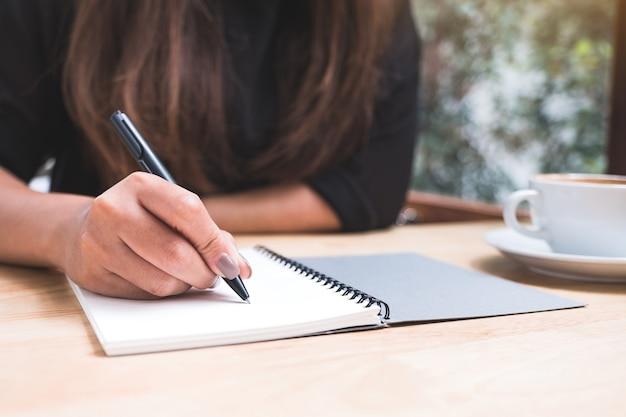 木製のテーブルの上のコーヒーカップと白い空白のノートに書き留めている女性の手のクローズアップ画像