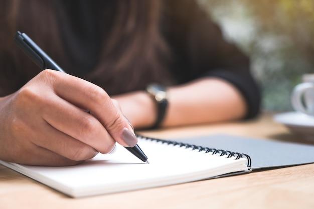 Изображение крупного плана руки женщины писать вниз на белой пустой тетради с кофейной чашкой на деревянном столе