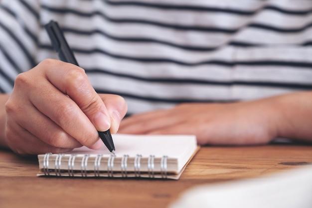 木製のテーブルの上の空白のノートに書いている女性の手のクローズアップ画像