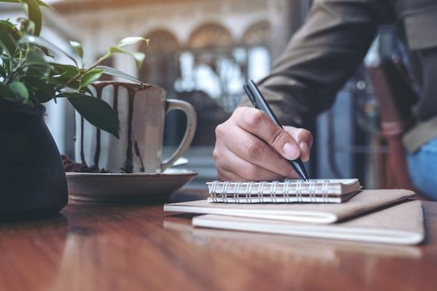 木製のテーブルの上のコーヒーカップと空白のノートに書く女性の手のクローズアップ画像