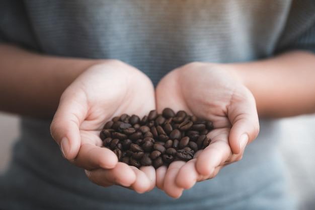 Крупным планом изображение женских рук, холдинг и показ кофейных зерен