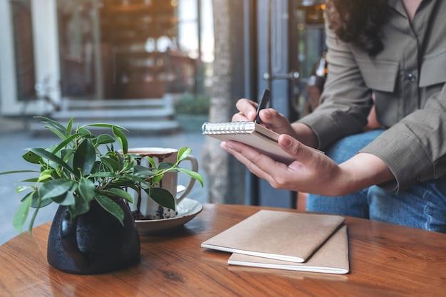 Крупным планом изображение женских рук, держащихся и пишущих на пустом блокноте с чашкой кофе на деревянном столе