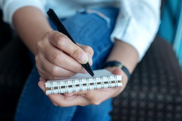 Крупным планом изображение руки женщины, держащей и записывающей на пустой блокнот