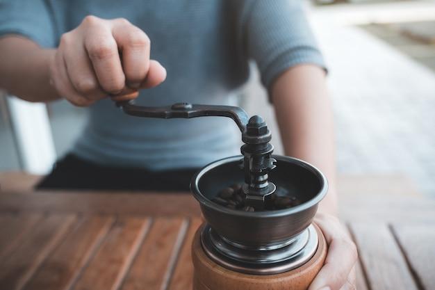 Крупным планом изображение женских рук, использующих старинную деревянную кофемолку для измельчения кофейных зерен