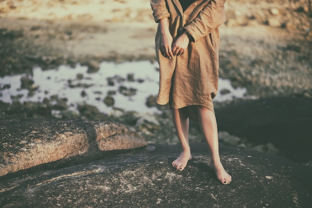 Крупным планом изображение женских ног, стоя на скале у пляжа