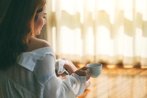 아침에 바닥에 앉아 뜨거운 커피 한 잔을 들고 있는 여성의 클로즈업 이미지