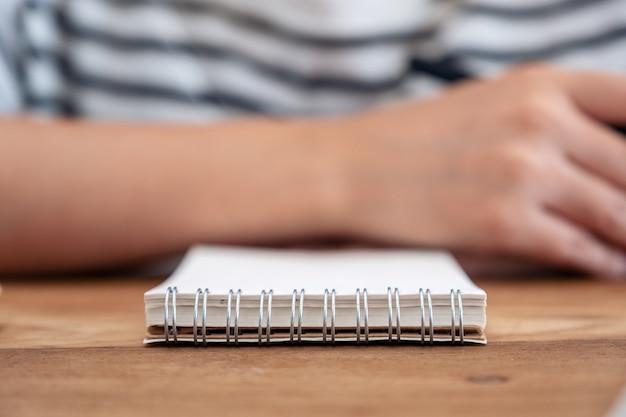 木製のテーブルに空白のノートブックと座っている女性のクローズアップ画像