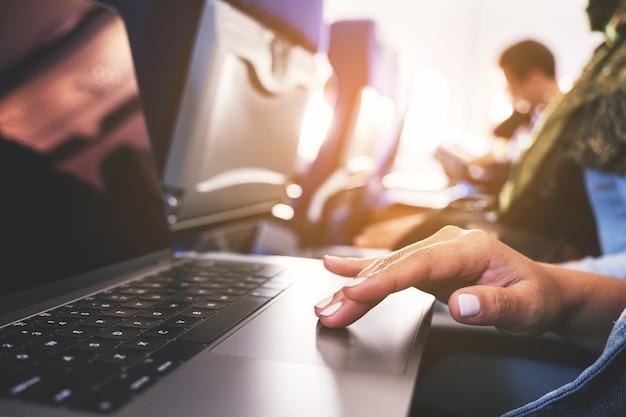 오두막에 앉아있는 동안 노트북 컴퓨터 터치 패드를 사용하고 만지는 여자의 근접 촬영 이미지
