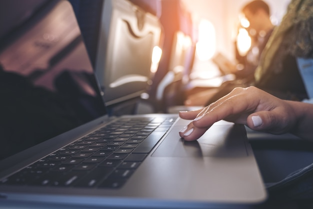 Крупным планом изображение женщины, использующей и касаясь сенсорной панели портативного компьютера, сидя в кабине