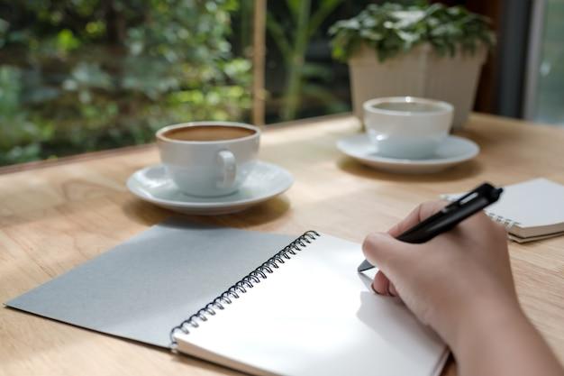 Изображение крупного плана женщины записывая вниз на белой пустой тетради с кофейной чашкой на деревянном столе