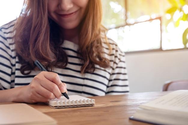 学習しながら空白のノートブックと木製のテーブルの本に書いている女性のクローズアップ画像