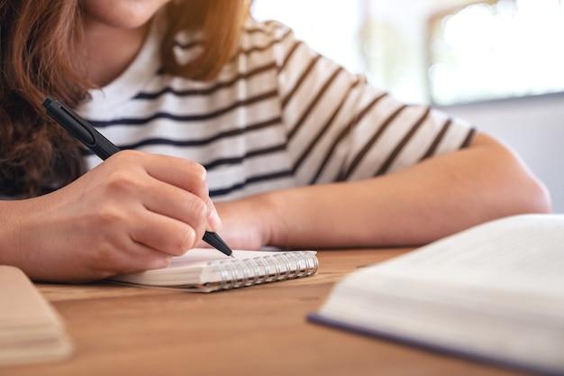학습하는 동안 나무 테이블에 책과 함께 빈 노트북에 쓰는 여자의 근접 촬영 이미지