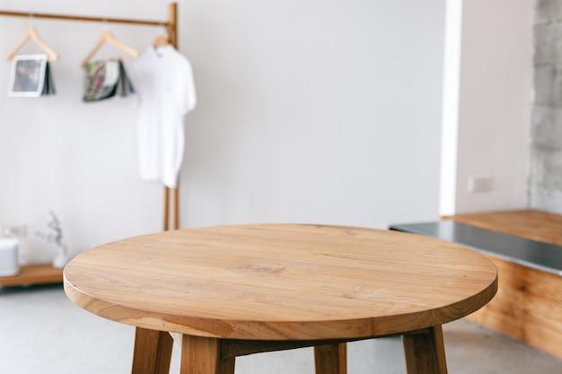 미니멀한 집에서 나무 테이블과 옷 순위의 근접 촬영 이미지