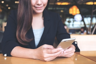 Closeup image of an asian businesswoman holding, using and looking at smartphone