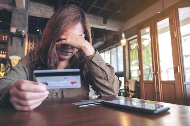 ストレスと壊れた感じ、テーブルの上の携帯電話でクレジットカードを保持しているアジアの女性のクローズアップ画像