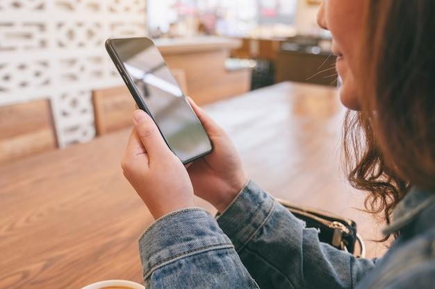 Крупным планом изображение азиатской женщины, держащей, использующей и смотрящей на смартфон в кафе