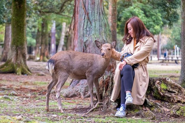Крупным планом изображение азиатской женщины, сидящей и играющей с диким оленем в парке