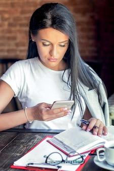 Крупным планом изображение бизнес-леди держит, использует и смотрит в кафе смарт-телефон.