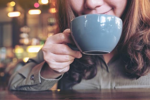 カフェで気分が良いと熱いコーヒーを嗅いで飲んでいるアジアの女性のクローズアップ画像