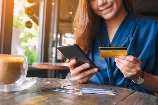 携帯電話でオンラインで購入や買い物にクレジットカードを使用してアジアの女性のクローズアップ画像