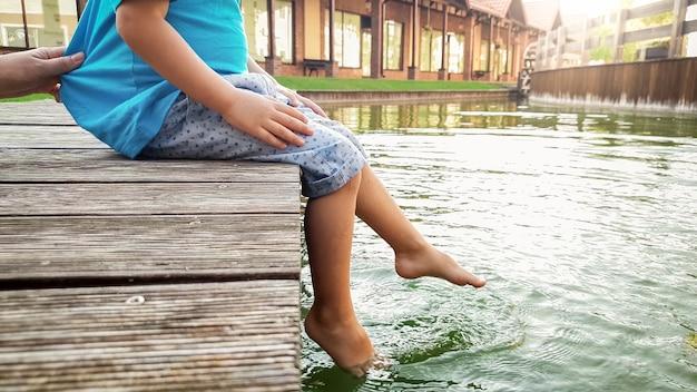 湖の木製の橋の上に座って、足で水をはねかける裸足の小さな幼児の少年のクローズアップ画像