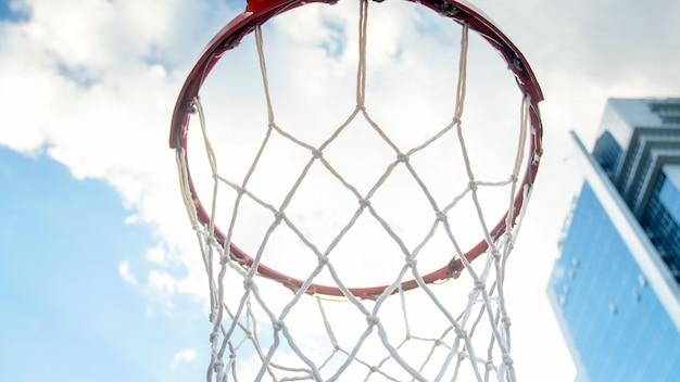 구름과 푸른 하늘에 대 한 스포츠 운동장에 그물 농구 링의 근접 촬영 이미지