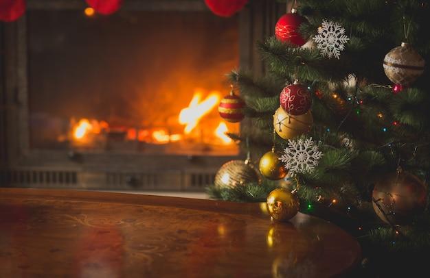 燃える暖炉の前のクリスマスツリーのつまらないもののクローズアップ画像。美しいクリスマスの背景