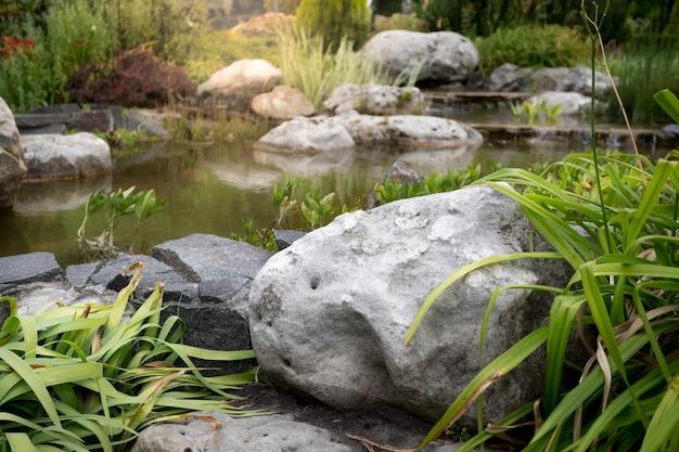 Крупным планом изображение большого валуна в быстрой реке в садовом парке