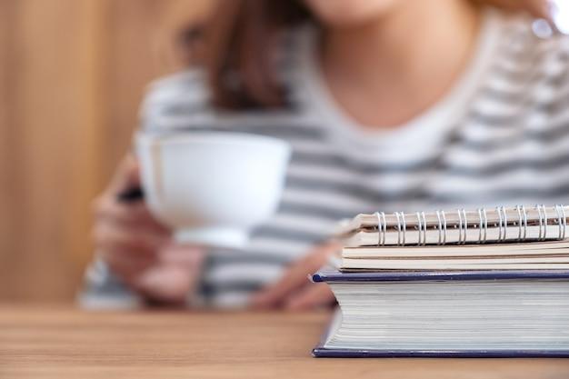背景にコーヒーを飲むぼやけた女性と木製のテーブルの上の本やノートブックのクローズアップ画像