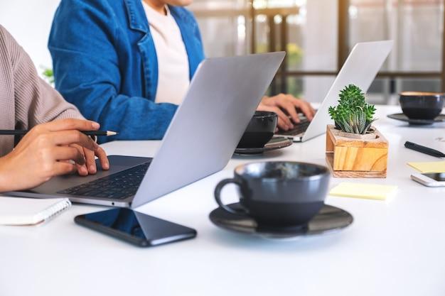 一緒にオフィスでラップトップコンピューターを使用して作業しているビジネスマンのクローズアップ画像