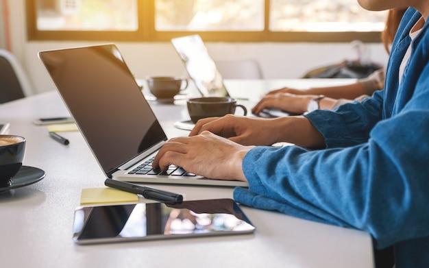 オフィスのテーブルにタブレットpcを使用してラップトップコンピューターで作業しているビジネスマンのクローズアップ画像