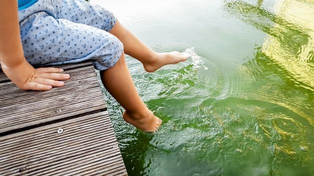 Tiverで木製の桟橋に座って、水中で足を保持している子供のクローズアップ画像。遊んでいる子供たちと足で水をはねかける