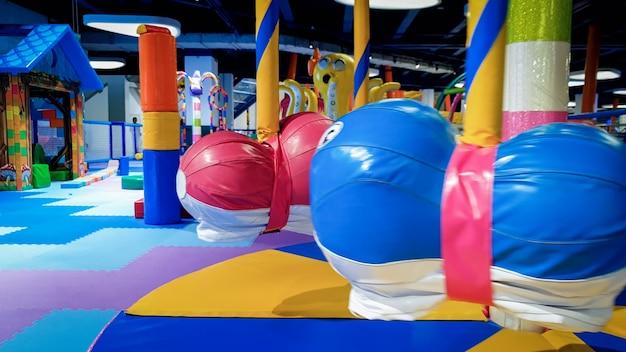 Крупным планом изображение красочной детской карусели и качелей на детской площадке, покрытой мягкими циновками для безопасности детей