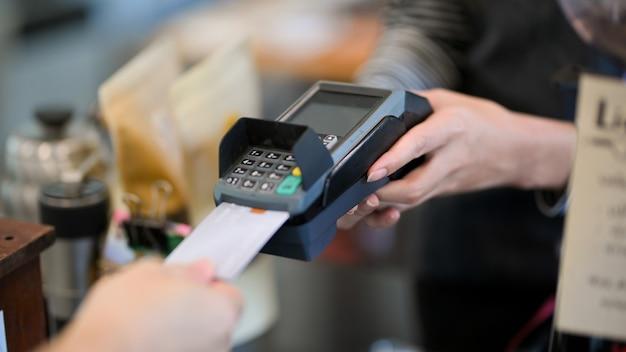 コーヒーショップでコーヒードリンクを支払うために支払い機にクレジットカードを挿入する顧客のクローズアップ画像 Premium写真