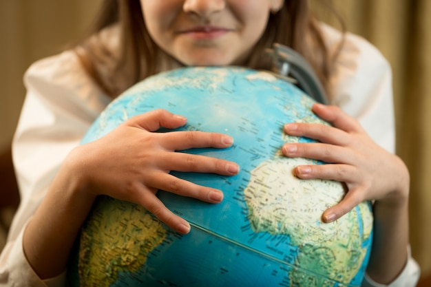 地球上で手をつないでかわいい女の子のクローズアップ画像。地球保護の概念