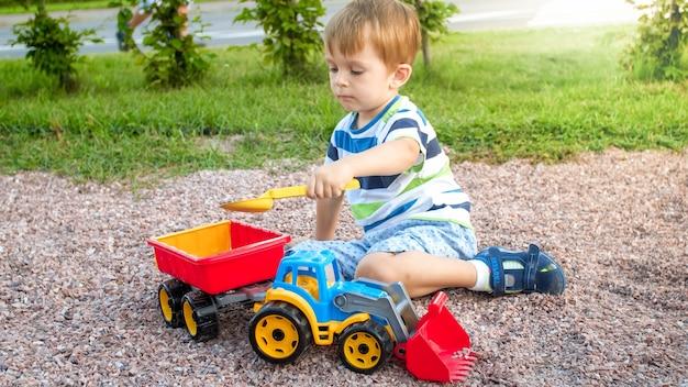 장난감 palyground에서 재생하는 귀여운 어린 소년의 근접 촬영 이미지. 트럭, 굴삭기 및 트레일러와 함께 재미 자식