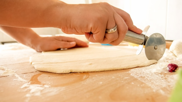 ピザの丸いナイフを持って、キッチンの大きな木製の机の上で生地を切る女性の手のクローズアップ画像