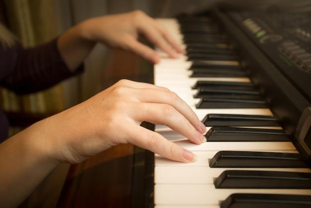 ピアノで遊ぶ女性の手のクローズアップ画像