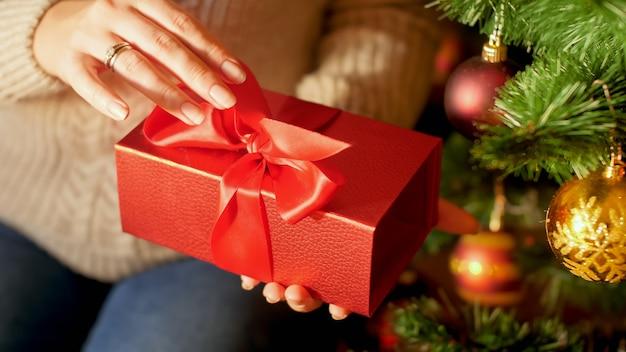 Крупным планом изображение женских рук, тянущих красную ленту и открывающих коробку рождественских подарков из санты