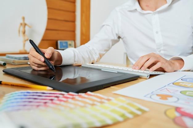顧客と絵を描くための大きなプロジェクトに取り組んでいるフリーランスのグラフィックデザイナーのクローズアップ画像...