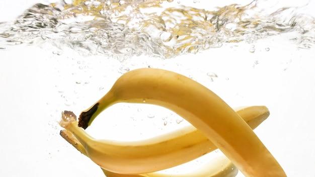 熟した新鮮なバナナが落下し、水しぶきのクローズ アップ画像