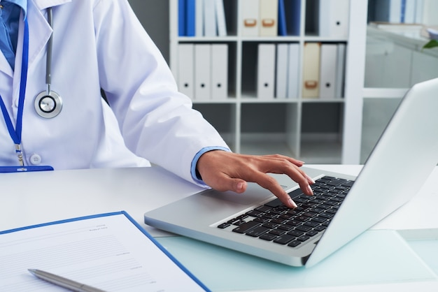 ノートパソコンで作業し、彼女のオフィスの机で文書に署名する一般開業医のクローズアップ画像