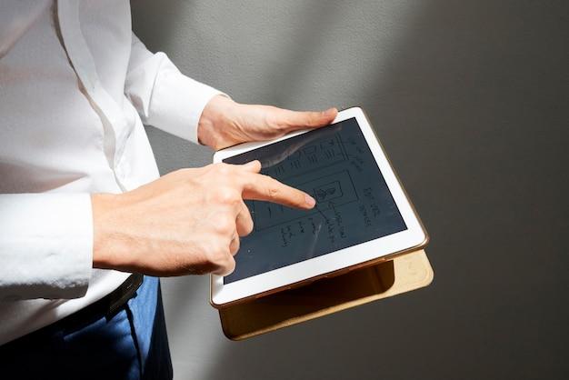 デジタルタブレット上のモバイルアプリケーションまたはウェブサイトのレイアウトを描くグラフィックデザイナーのクローズアップ画像..。