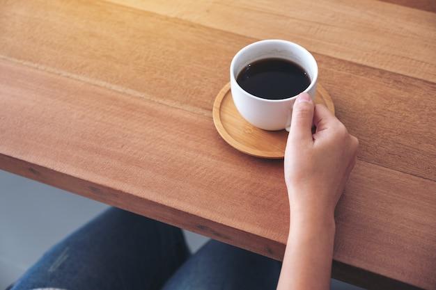 木製のテーブルで飲むためにホットコーヒーの白いカップを持っている手のクローズアップ画像